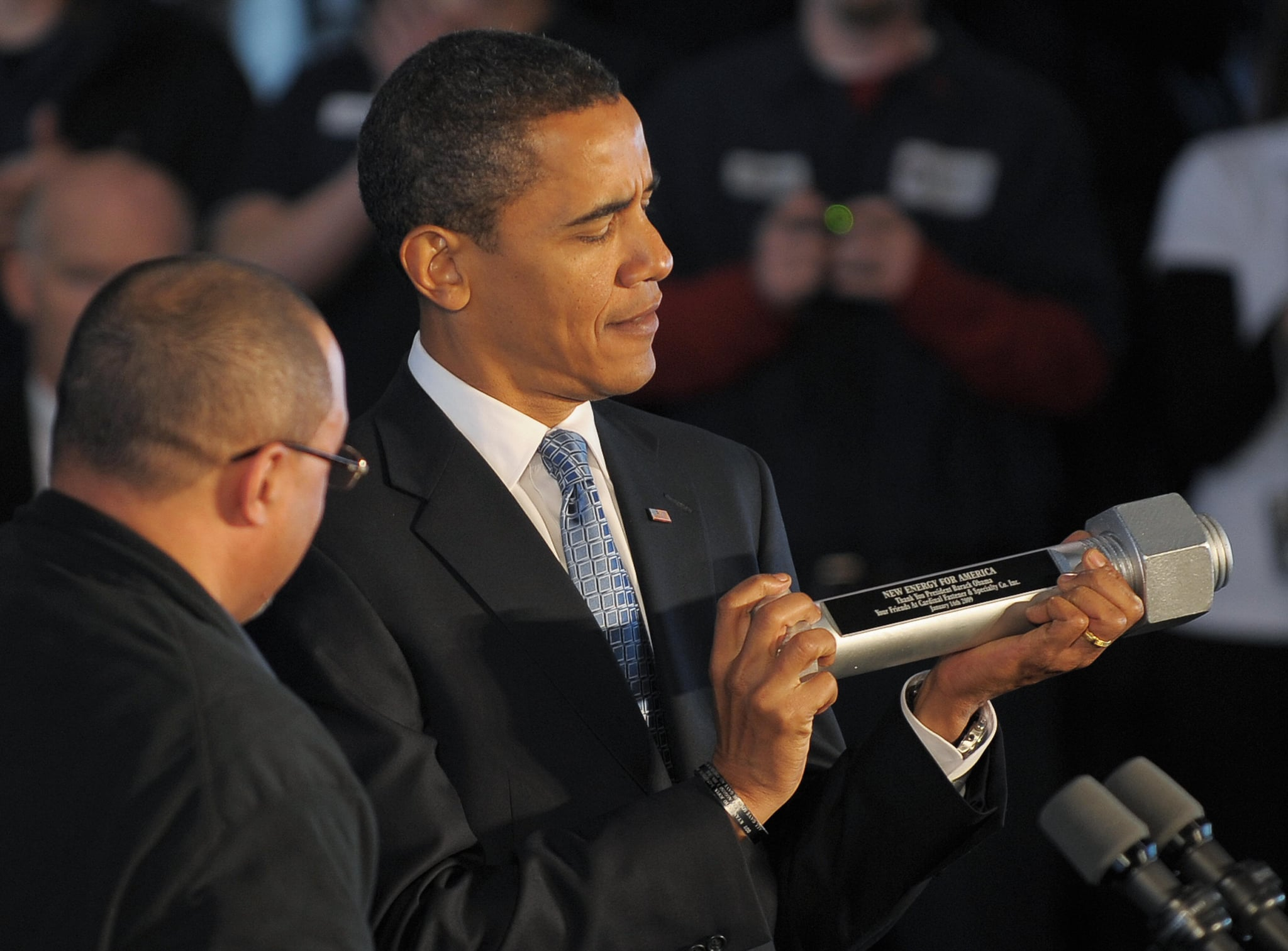 Obama holds a souvenir bolt presented to him by an employee following the tour.