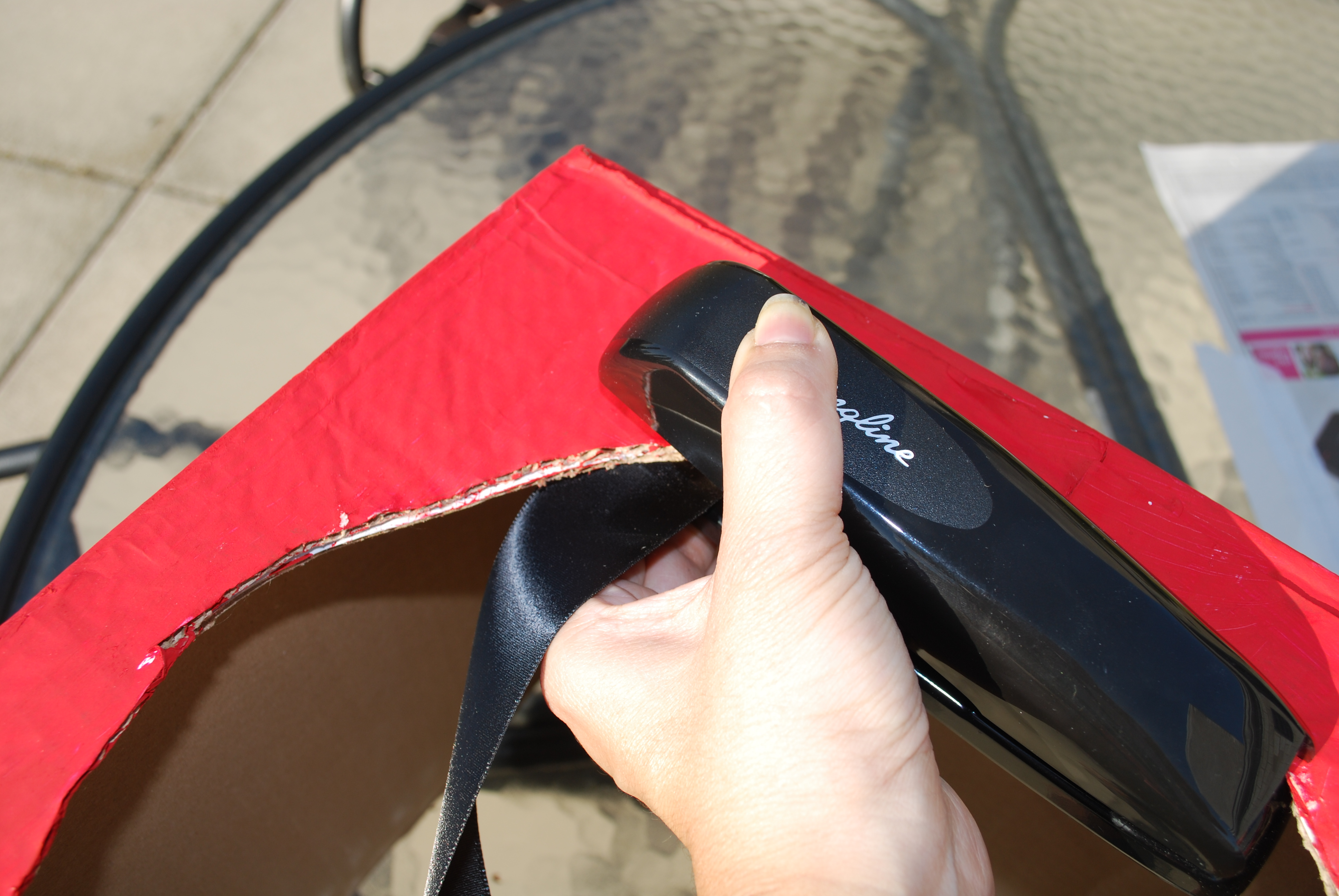 Staple each ribbon to the underside of the body of the fire engine.